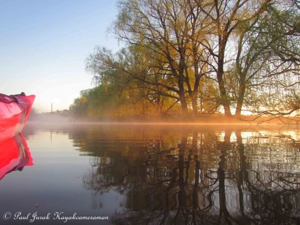 A narrow beam of light  highlights the morning mist.